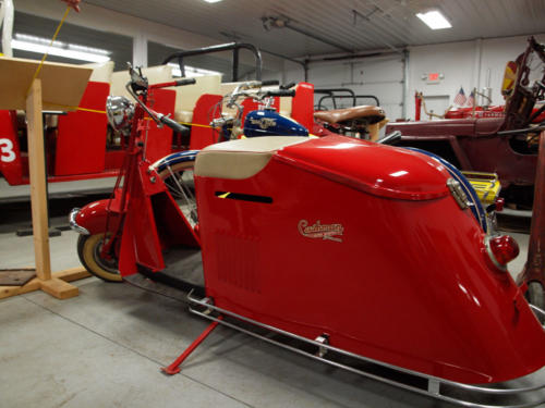 MotorCycle-Cushman-Red&White-DriverSideFromBackToFront-7228859